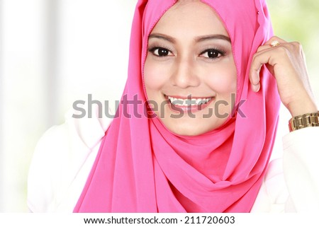 portrait of young attractive asian woman wearing head scarf - stock photo