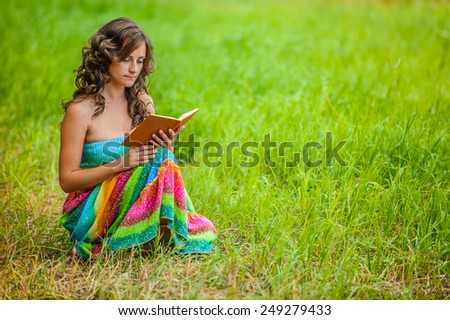 Portrait of young attractive beautiful dark-haired curly woman holding book at summer green park. - stock photo