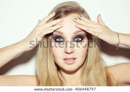 Portrait of young attractive blond woman touching her wrinkled forehead with worried expression - stock photo