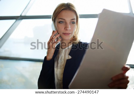 Portrait of young attractive business woman having cell phone conversation while examining paperwork in light office interior sitting next to the window, filtered image, soft focus - stock photo