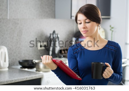 Portrait of young attractive caucasian brunette housewife at kitchen. Morning with cup of coffee and tablet pc. - stock photo