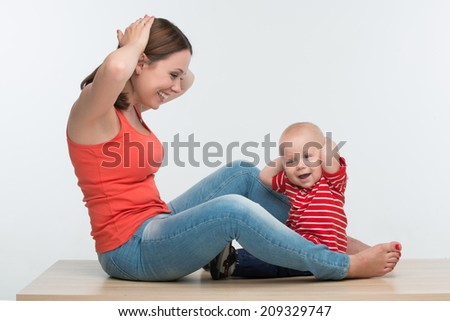 Portrait of young attractive Caucasian mother sitting face to face to her cute toddler son playing with hands on head, lifestyle fun concept, isolated on white - stock photo