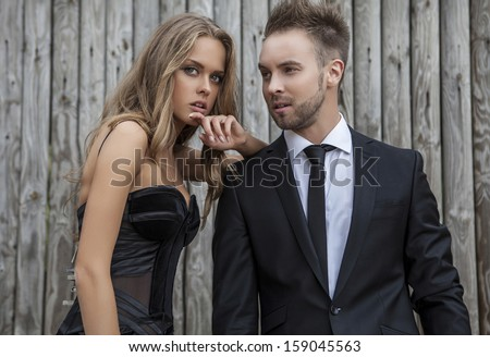 Portrait of young attractive couple posing outdoor dressed in black fashionable clothes.  - stock photo