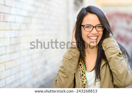 Portrait of young attractive girl in urban background hearing music with headphones - stock photo