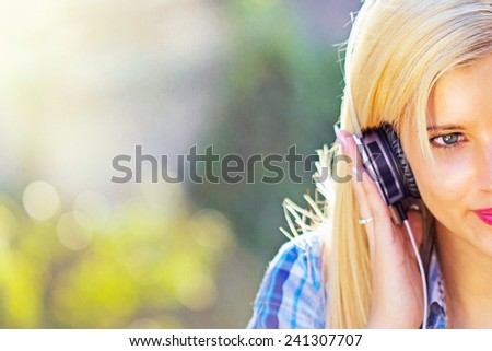 Portrait of young attractive girl listening to music with headphones - stock photo