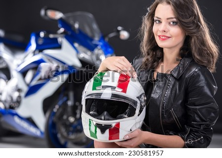 Portrait of young attractive girl with helmet and motorcycle on black background. - stock photo