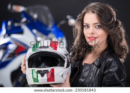Portrait of young attractive girl with helmet. The motorcycle is on black background. - stock photo