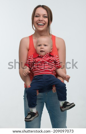 Portrait of Young attractive mother and her cute toddler son having fun, toothy smile, isolated on white - stock photo