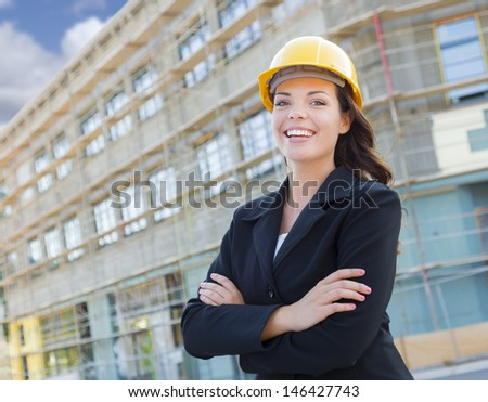 Portrait of Young Attractive Professional Female Contractor Wearing Hard Hat at Construction Site. - stock photo