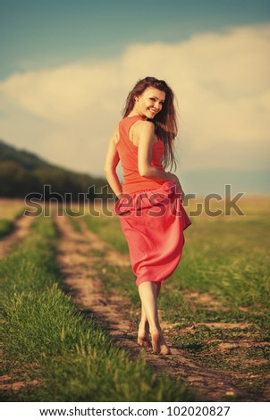 Portrait of young attractive smiling woman walking on the road outdoor in summer - stock photo