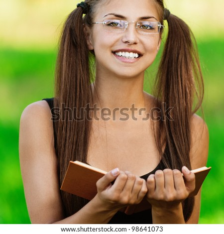 Portrait of young attractive smiling woman wearing black blouse and eyeglasses standing at summer green park. - stock photo