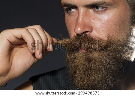 Portrait of young attractive unshaven guy with beard touching moustache with hand looking away on black studio background, horizontal picture - stock photo