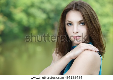 Portrait of young attractive woman embracing herself at summer green park. - stock photo