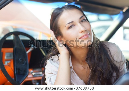 Portrait of young attractive woman in the car - stock photo