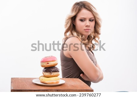Portrait of young attractive woman looking at doughnuts doubtfully isolated on white background, diet concept - stock photo