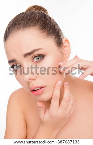 portrait of young attractive woman looking for acne on her face - stock photo