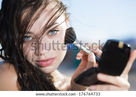 Portrait of young attractive woman posing with a brush for makeup - stock photo