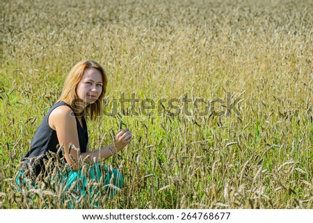 Portrait of young attractive woman sitting in field - stock photo