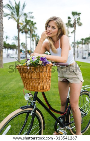 Portrait of young attractive woman standing with her vintage bike on green grass in the park while rest after riding in the city,wonderful blonde female posing with her classic bicycle in a summer day - stock photo