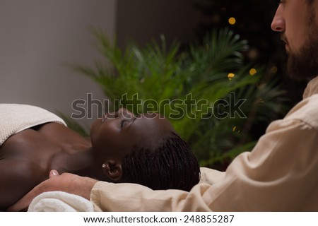 Portrait of young beautiful african woman in spa environment getting massage - stock photo