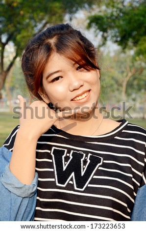 Portrait of young beautiful Asian woman make a hand sign like telephone. - stock photo