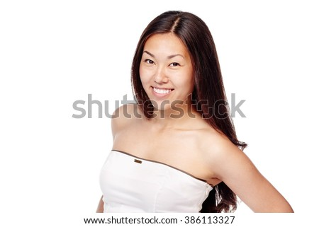 Portrait of young beautiful asian woman with long brown hair and fresh makeup wearing white dress and smiling isolated on white background - beauty concept - stock photo