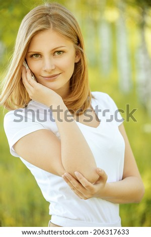portrait of young beautiful blond woman in white blouse speaking on mobile phone and standing at park - stock photo