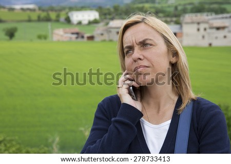 portrait of young beautiful blond woman speaking on mobile phone and standing at park - stock photo