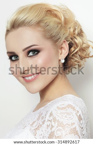 Portrait of young beautiful blonde happy smiling bride in lacy dress - stock photo