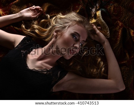 Portrait of young beautiful blonde with gold Venetian mask - stock photo