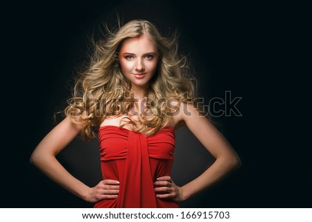 Portrait of young beautiful blonde woman in red dress - stock photo