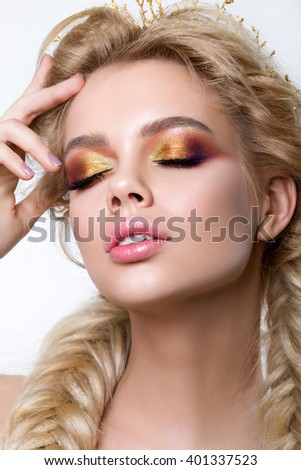 Portrait of young beautiful blonde woman with modern creative make-up and fishtail braids wearing golden crown. Multicolored smokey eyes and perfect brows - stock photo