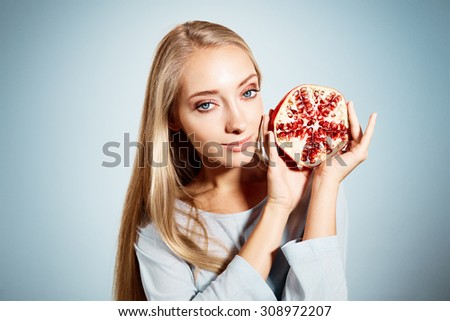 Portrait of young beautiful blonde woman with pomegranates in her hands isolated on blue background - stock photo