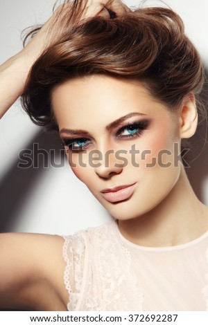 Portrait of young beautiful blue-eyed smiling woman with stylish make-up touching her hair - stock photo