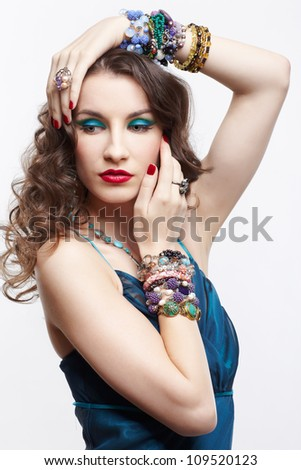portrait of young beautiful brunette woman in blue dress and jewelery touching her head with manicured hands - stock photo