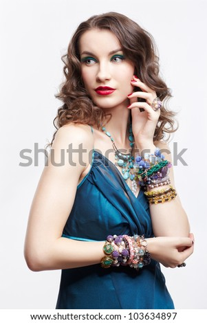 portrait of young beautiful brunette woman in blue dress and various jewelery - stock photo