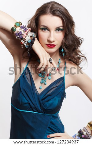 portrait of young beautiful brunette woman in blue dress, in beads, ear-rings, rings and bracelets - stock photo