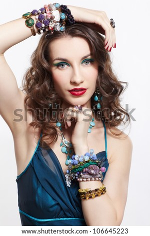 portrait of young beautiful brunette woman in blue dress in in rings, bracelets, ear-rings and beads on gray - stock photo