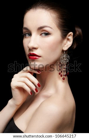portrait of young beautiful brunette woman in ear-rings on black touching her chin with manicured fingers - stock photo
