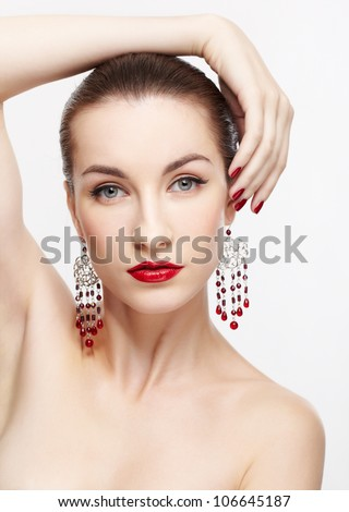 portrait of young beautiful brunette woman in jewelery on gray touching her hair with manicured fingers - stock photo