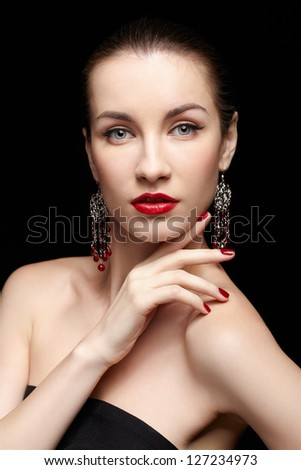 portrait of young beautiful brunette woman in jewelery touching shoulder with manicured fingers - stock photo
