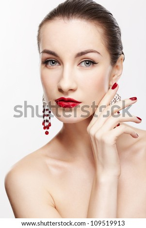 portrait of young beautiful brunette woman in jewelery with manicured fingers on gray - stock photo