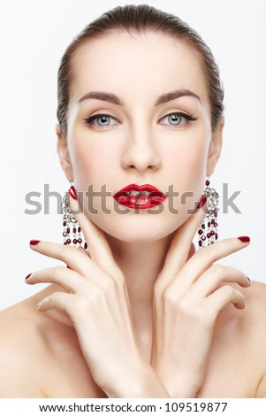 portrait of young beautiful brunette woman in jewellery on gray - stock photo
