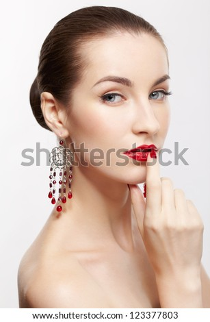 portrait of young beautiful brunette woman in jewellery on gray touching her lips with manicured finger - stock photo