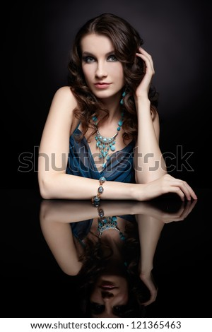 portrait of young beautiful brunette woman in jewellery sitting at black reflecting table - stock photo
