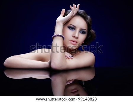 portrait of young beautiful brunette woman in jewelry at reflecting table on blue - stock photo