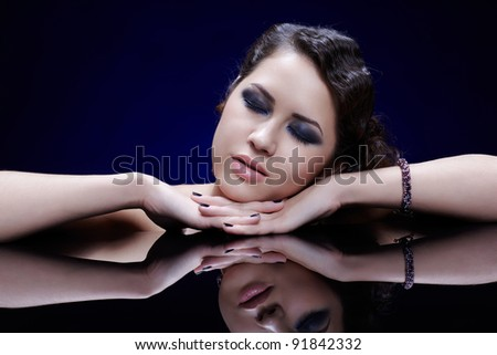portrait of young beautiful brunette woman in jewelry sitting at reflecting table with eyes shut - stock photo