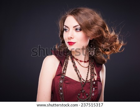 Portrait of young beautiful brunette woman in jewelry standing over black background. Vogue style. Studio shot. Perfect hair and skin. - stock photo