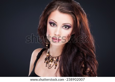 Portrait of young beautiful brunette woman in jewelry standing over black background. Vogue style. Studio shot. Perfect makeup, hair and skin. - stock photo