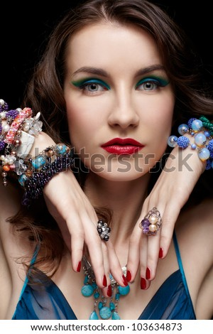 portrait of young beautiful brunette woman in rings, bracelets and beads on black - stock photo
